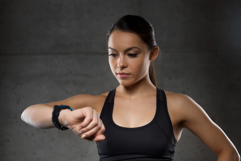 Fit Woman Looking At Her FitBit Fitness Tracker